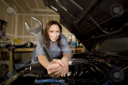 Hispanic woman in garage with wrench stock photo, Pretty Hispanic woman with wrench working on car in garage by Scott Griessel