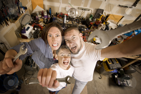 Crazy Do-It-Yourself family with wrenches stock photo, Crazy Hispanic family in garage with crescent wrenches by Scott Griessel