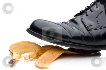 Black leather business shoe about to slip on a bannana peel stock photo, Black leather business shoe about to slip on a bannana peel by Vince Clements