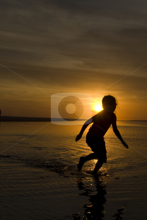 Sunset Silhouette Girl Running stock photo, A young girl playing in a wading pool at the beach as the sun sets behind her by A Cotton Photo