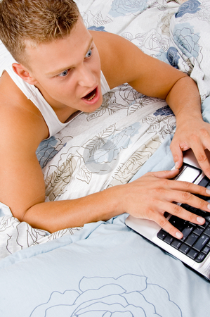 Man working on laptop at home and stock photo, Handsome man working on laptop at home in bed by Imagery Majestic