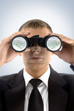 Successful businessman looking at currency text  stock photo, Successful businessman looking at currency text with binoculars by Imagery Majestic