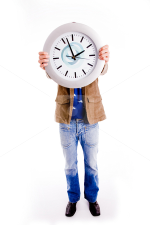 What time is it - clock stock photo, Front view of young man hiding his face with watch on an isolated background by Imagery Majestic