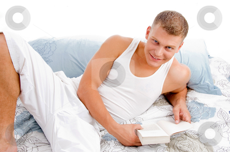 Young man reading book in bed stock photo, Smart fellow interested in reading books in bed by Imagery Majestic