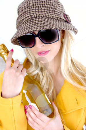 Front view of fashionable woman holding wine bottle stock photo, Front view of fashionable woman holding wine bottle with white background by Imagery Majestic