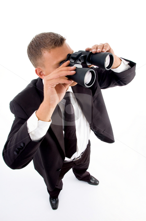 Young accountant looking through binoculars stock photo, Young accountant looking through binoculars on an isolated white background by Imagery Majestic