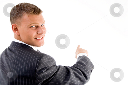 Smiling handsome employee pointing back stock photo, Smiling handsome employee pointing back side on an isolated background by Imagery Majestic