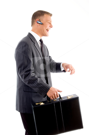 Successful businessman smiling and holding office bag stock photo, Successful businessman smiling and holding office bag against white background by Imagery Majestic