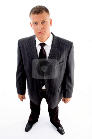 Handsome businessman looking at camera stock photo, Handsome businessman looking at camera on an isolated background by Imagery Majestic