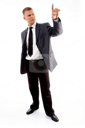 Standing lawyer looking at his index finger stock photo, Standing lawyer looking at his index finger against white background by Imagery Majestic