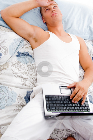 Man resting with laptop stock photo, Man resting at his home with laptop and looking upwards in bed by Imagery Majestic