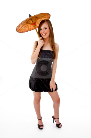 Front view of young woman holding umbrella stock photo, Front view of young woman holding umbrella against white background by Imagery Majestic