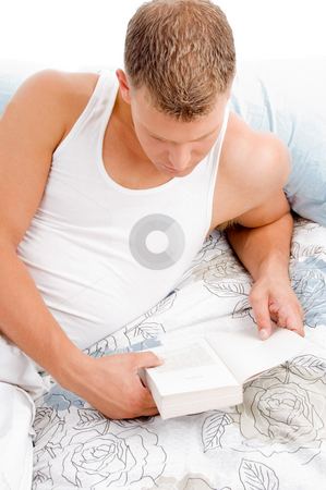 Lying in bed and reading book stock photo, Man lying on bed and reading book against white background by Imagery Majestic