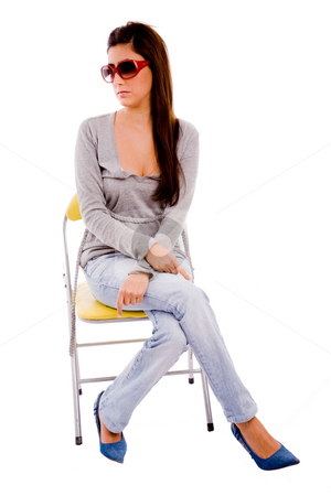 Front view of young woman sitting on chair stock photo, Front view of young woman sitting on chair with white background by Imagery Majestic