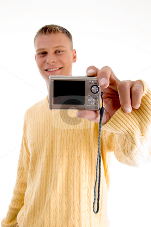 Blonde man showing digital camera  stock photo, Blonde man showing digital camera on an isolated background by Imagery Majestic