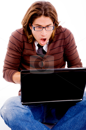 Front view of shocked man looking at laptop stock photo, Front view of shocked man looking at laptop with white background by Imagery Majestic