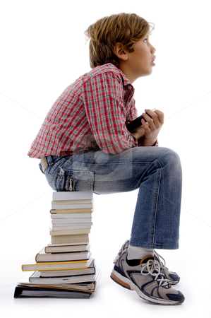 Thinking student with books copyspace stock photo, Top view of boy sitting on stack of books with white background by Imagery Majestic