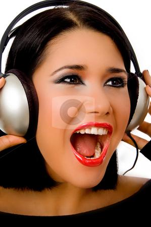 Portrait of happy beautiful female listening music stock photo, Portrait of happy beautiful female listening music on an isolated background by Imagery Majestic