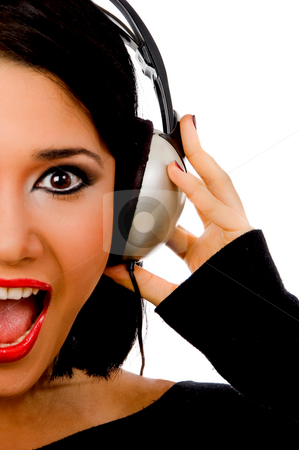 Portrait of happy young female listening music stock photo, Portrait of happy young female listening music on an isolated background by Imagery Majestic