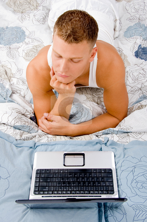 Working on PC in bed relaxing stock photo, Man resting and thinking something in bed by Imagery Majestic