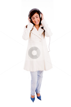 Front view of young woman enjoying music stock photo, Front view of young woman enjoying music with white background by Imagery Majestic