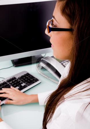 Woman working on computer stock photo, Side pose of woman working on computer against white background by Imagery Majestic