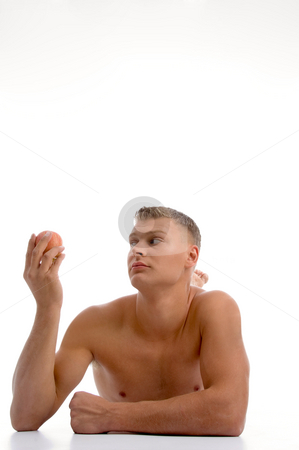 Laying muscular male looking the apple stock photo, Laying muscular male looking the apple against white background by Imagery Majestic