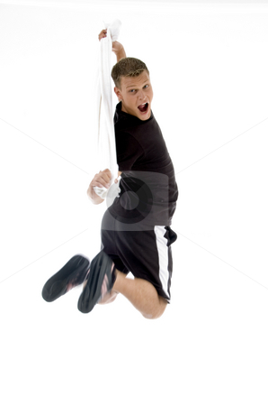 Jumping man holding towel stock photo, Jumping man holding towel against white background by Imagery Majestic