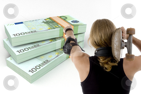 Man pointing the bundles of euro note with skateboard  stock photo, Back pose of man pointing the bundles of euro notes with skateboard by Imagery Majestic