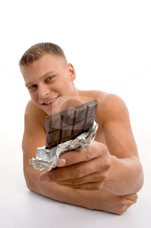 Smiling muscular man showing chocolate stock photo, Smiling muscular man showing chocolate against white background by Imagery Majestic