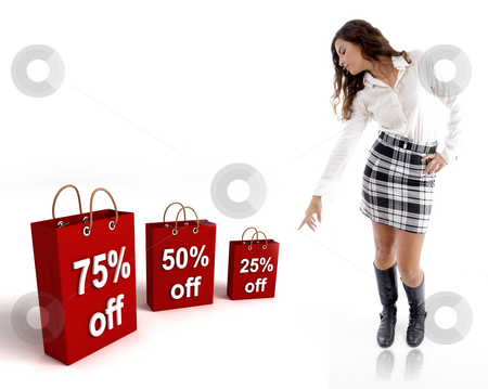 Pretty woman pointing the shopping bags stock photo, Pretty woman pointing at the  three dimensional shopping bags against white background by Imagery Majestic