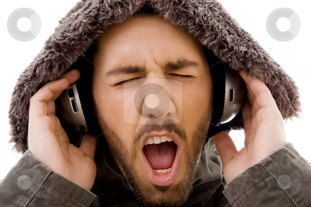 Close up of shouting male listening to music  stock photo, Close up of shouting male listening to music on an isolated white background by Imagery Majestic