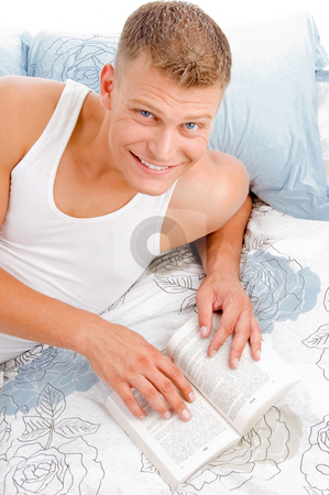 Portrait of guy reading a book stock photo, Smart fellow interested in reading books in bed by Imagery Majestic