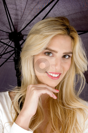 Front view of smiling woman holding an umbrella stock photo, Front view of smiling woman holding an umbrella by Imagery Majestic