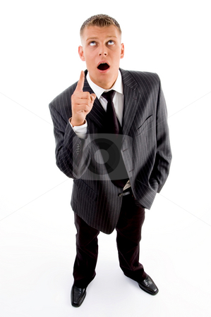 Shocked standing businessman pointing upside stock photo, Shocked standing businessman pointing upside against white background by Imagery Majestic