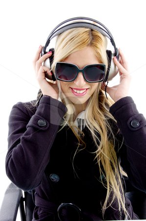 Front view of smiling woman listening music stock photo, Front view of smiling woman listening music on an isolated background by Imagery Majestic