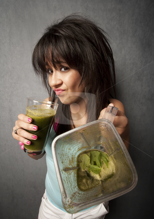 Pretty girl with unappetizing health shake stock photo, Pretty girl grimacing and holding unappetizing blended health shake by Scott Griessel