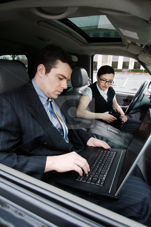 Road Warriors - Deep in Thought stock photo, A shot of a businessman and businesswoman sitting in a car looking at a laptop. by Orange Line Media
