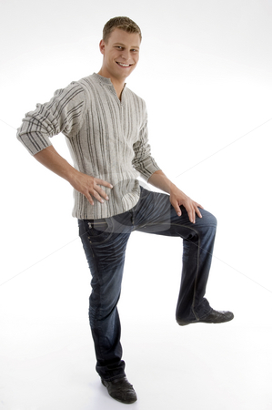 Smiling man standing on one leg stock photo, Smiling man standing on one leg on an isolated background by Imagery Majestic