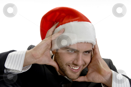 Man posing with santa cap and holding his face stock photo, Man posing with santa cap and holding his face on an isolated white background by Imagery Majestic