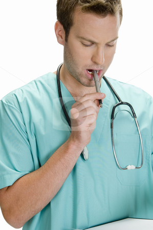 Doctor putting pen in his mouth and looking in writing pad stock photo, Doctor putting pen in his mouth and looking in writing pad by Imagery Majestic