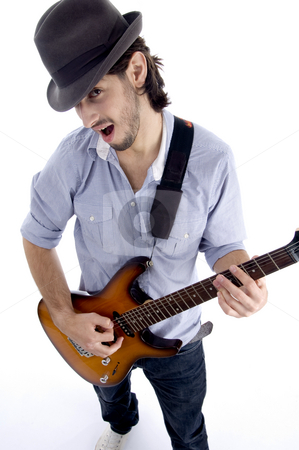 Handsome male looking at camera and playing guitar stock photo, Handsome male looking at camera and playing guitar on an isolated white background by Imagery Majestic