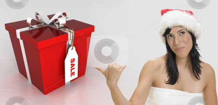 Sexy brunette woman wearing santa hat stock photo, Sexy brunette woman wearing santa cap and indicating towards the gift by Imagery Majestic