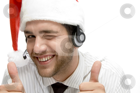 Happy businessman posing with cheer up stock photo, Happy businessman posing with cheer up and wearing santa cap by Imagery Majestic