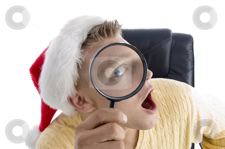 Man wearing santa hat and looking through lens stock photo, Man wearing santa hat and looking through lens on an isolated background by Imagery Majestic