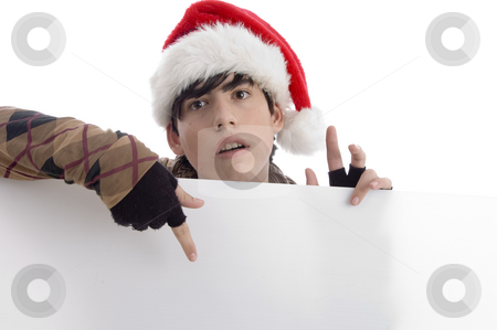 Young boy wearing christmas hat indicating placard stock photo, Young boy wearing christmas hat indicating placard with white background by Imagery Majestic