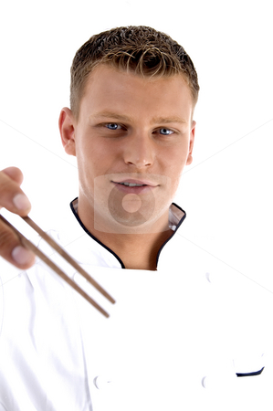 Handsome chef holding chopsticks stock photo, Handsome chef holding chopsticks on an isolated white background by Imagery Majestic