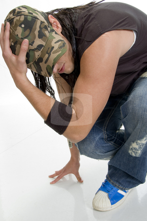 Sitting young male holding cap stock photo, Sitting young male holding cap by Imagery Majestic