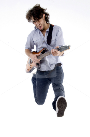 Young male jumping high holding his guitar stock photo, Young male jumping high holding his guitar isolated on white background by Imagery Majestic