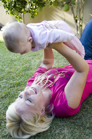 Beautiful mother playing with her newborn baby stock photo, Beautiful mother playing with her newborn baby in the garden by Imagery Majestic